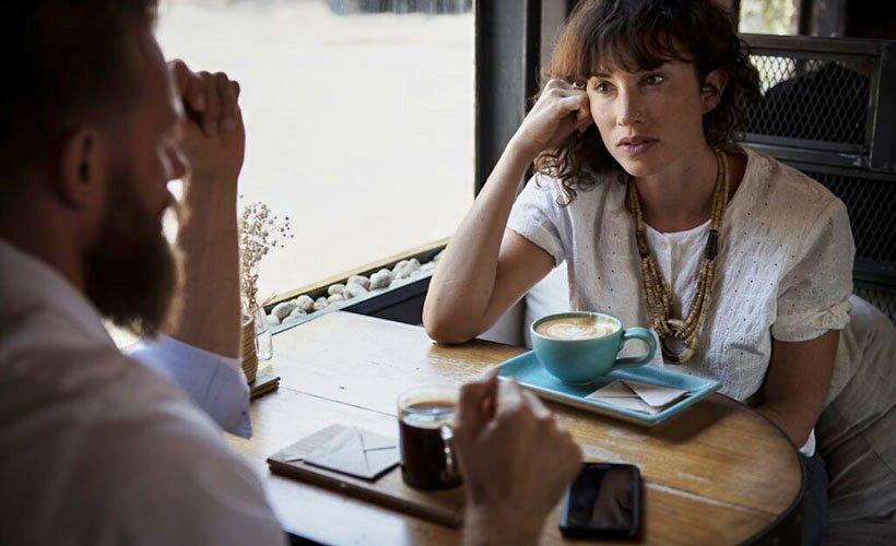 Auf Augenhöhe. Ein Paar sitzt an einem Tisch, trinkt Kaffee und unterhält sich.